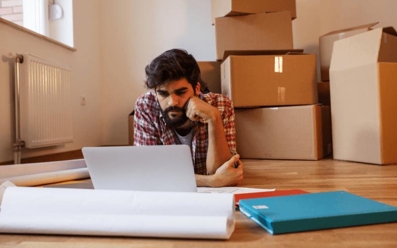 Mężczyzna z laptopem na podłodze.